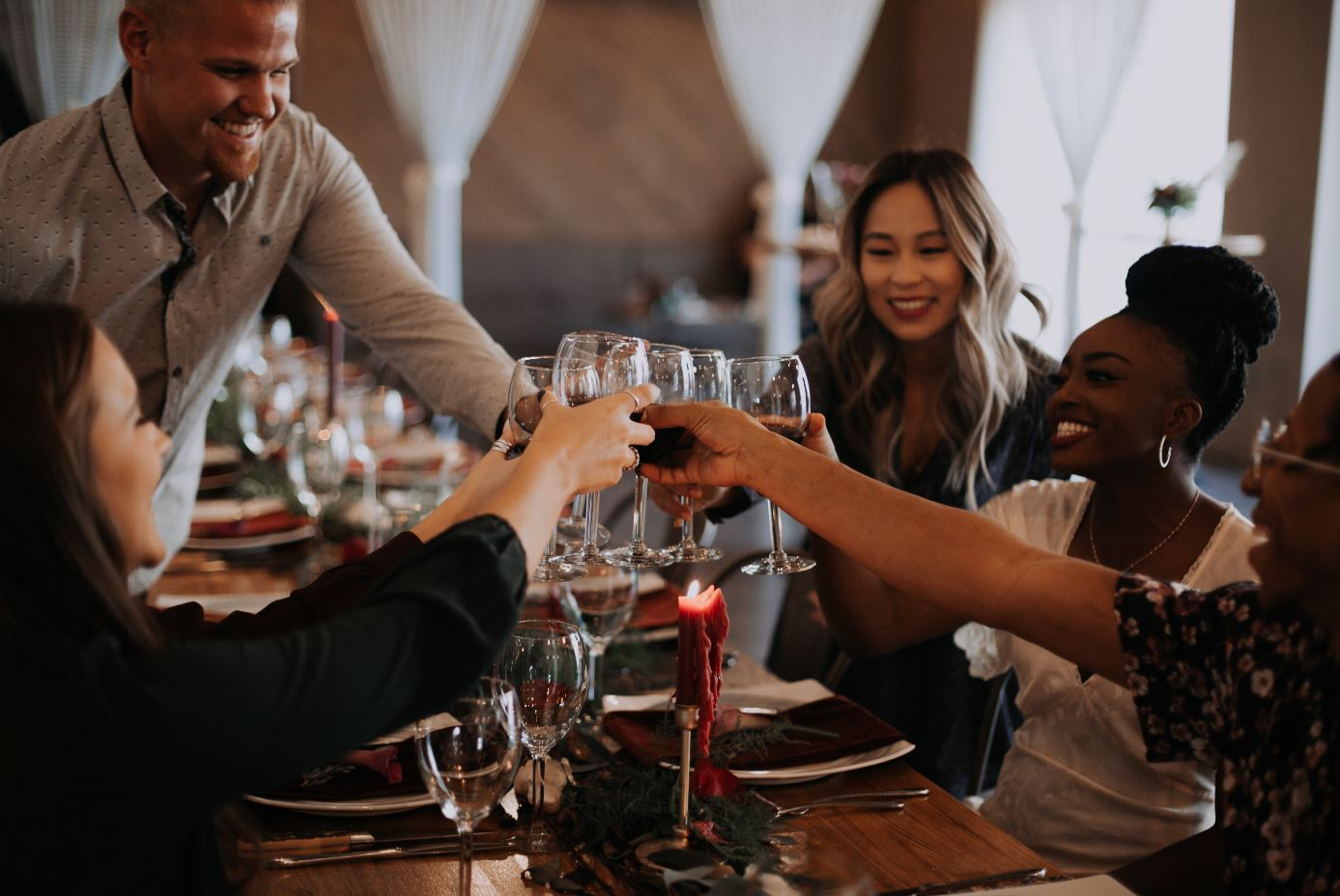 Friends gathered around a holiday table, raising a toast