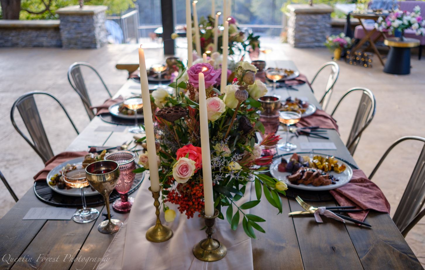 Table set for six with beautiful linens and lit taper candles